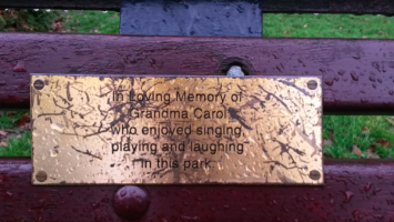 The dedication plaque on a park bench