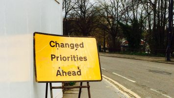 A road sign that says 'priorities changed ahead'
