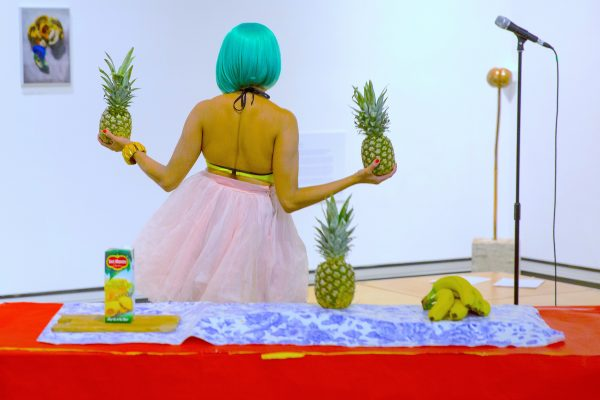 Priya Mistry holds two pineapples in front of a colourful table