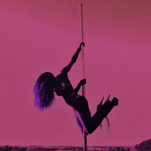 A dancer hangs from a pole, wearing heels and long curly hair, against a pink sky