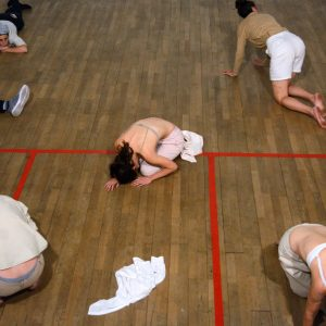 five people lie on a school gym floor