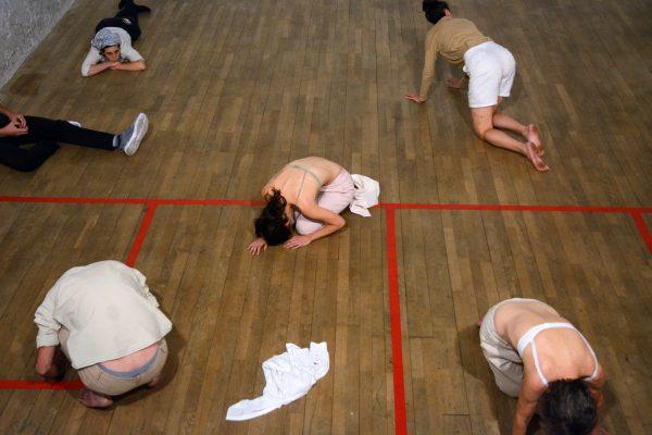five people lie on a school gym floor