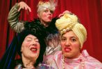 Three eccentric women take a selfie wearing makeup and brightly coloured outfits