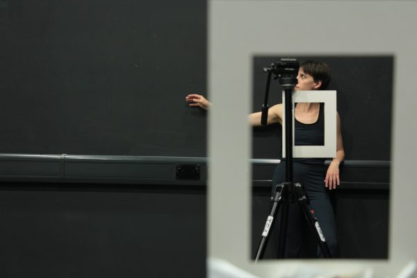 Various white frames are laid over an image of a dancer stood behind a camera