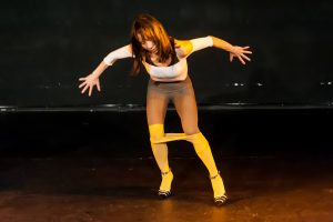 Jia-yu Corti stands with splayed limbs in yellow