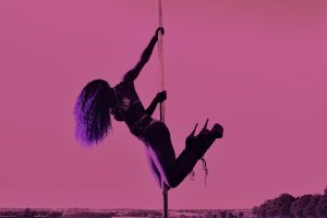 A dancer with long curly hair and stiletto heels hangs from a pole against a pink sly