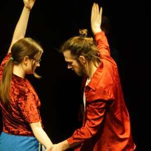 eleanor and lewys wearing red outfits facing towards each other, moving with one arm in the air