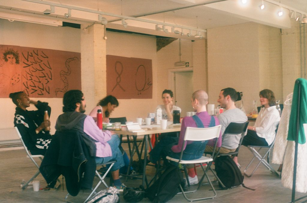 photograph of artists sitting around a table talking