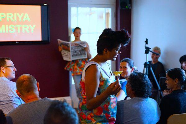 Priya smiling holding a piece of pineapple, stood amongst audience members
