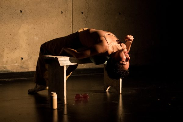 Mariana lays backwards over a bench, hand close to her mouth, on a dark stage