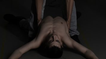 a dark image of a two hands holding the upper body of a man, lying backwards on the ground