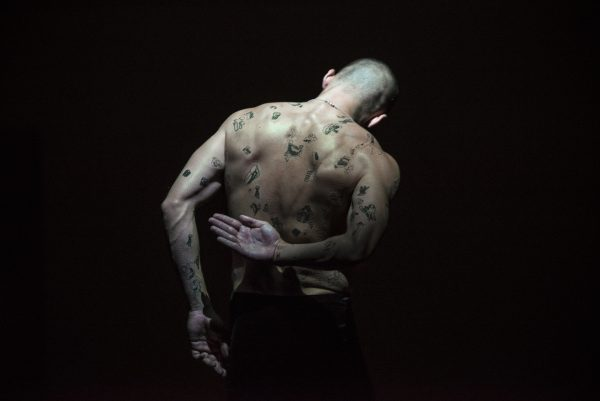 A moody image with James facing away from the camera exposing his back, covered in line drawings of body parts