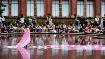 A male dancer stands in a fountain at the V&A, trailing long pink fabric through the water