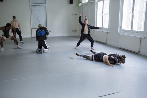 Dancers in a studio - one looks defiently at the camera with her hand in a fist
