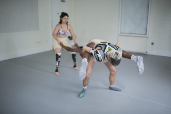 one dancers lays over the back of another, creating a geometric shape, wearing protections pads shoulders
