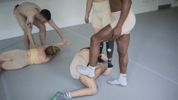 Five people wearing beige lycra shorts, holding parts of each others bodies. One performer has prosthetic legs
