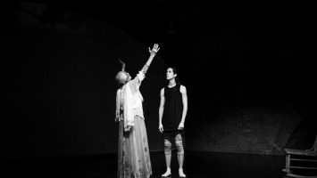 An older and a yung dancer stand on a dark stage