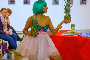 Priya wearing a brught blue wig, colourful outfit and holding a pineapple