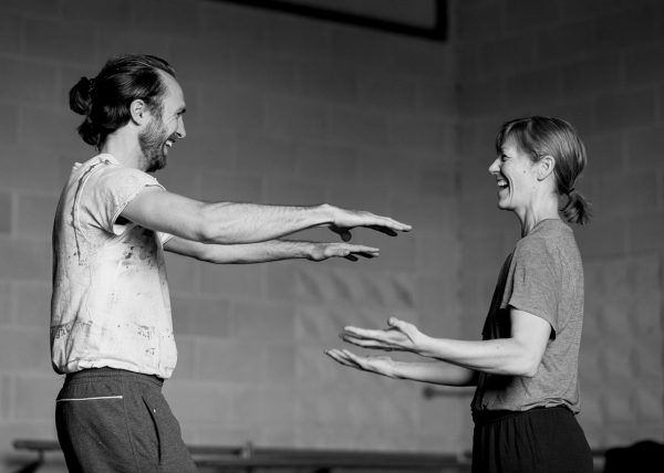 two laughing dancers stand facing each other, palms outstretched
