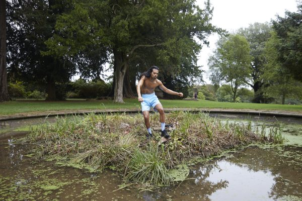 A dancer moving among reeds, their body wet