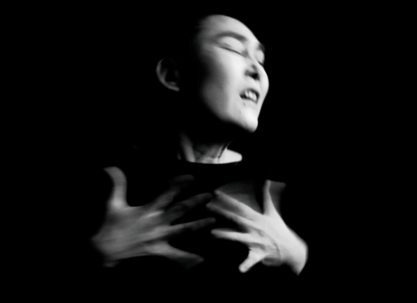 A person silouhetted against a black background, fingers outstretched and in motion