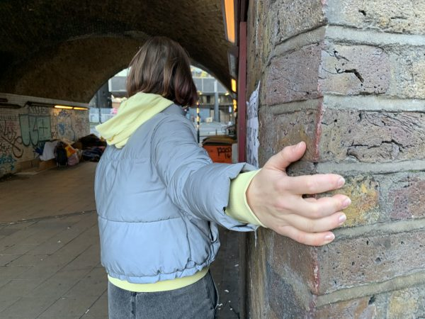 A hand grips the corner of a wall
