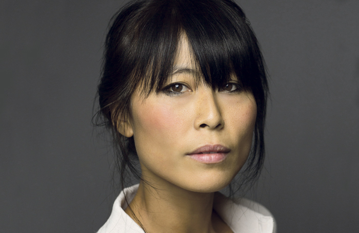 A photo of an East Asian woman. She has dark hair which is tied up, and a fringe which reaches her brown eyes